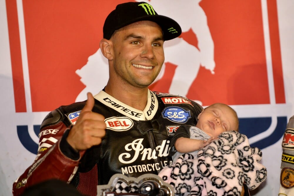 Jared Mees on the podium with his baby after winning the AFT National in Elbridge, NY