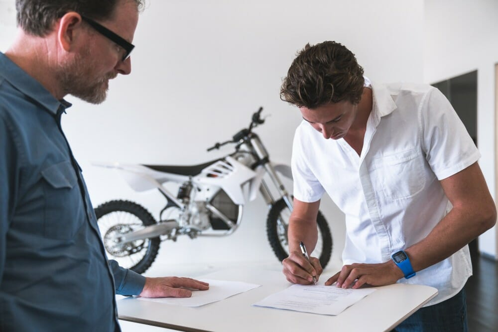 Ty Tremaine signs his Alta Motors contract along with Alta co-founder, Derek Dorrestyn.