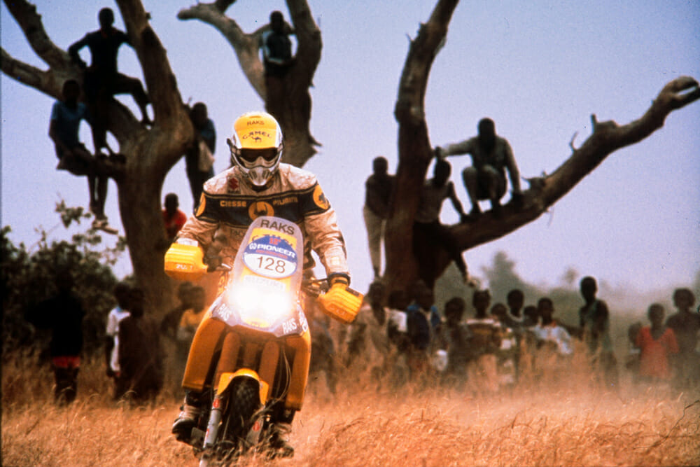 Gualini exits a village in Niger at the finish of the Special Stage on the Suzuki DR 750 Big.
