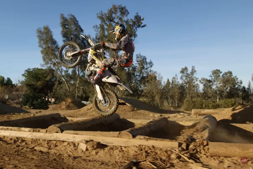 Colton Haaker jumping through the logs on his Husqvarna motorcycle.