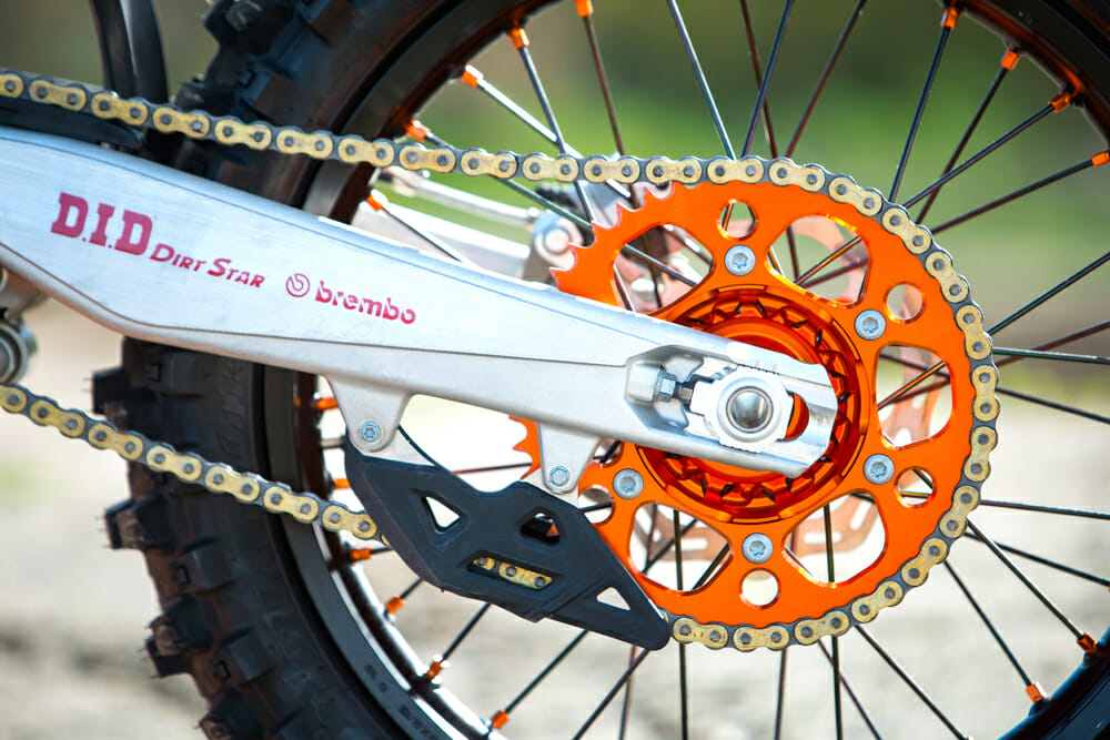 High-end components are everywhere, including the orange rear sprocket, orange spoke nipples, and D.I.D Dirt Star rims.