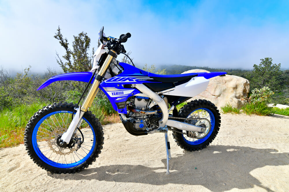The new WR shares many of the same off-road ingredients that set it and the 2019 YZ450FX apart from the YZ450F, like having an 18-inch rear wheel, wider gear ratios, larger fuel tank, tamer engine mapping, softer suspension, O-ring chain, skid plate, and a kickstand.