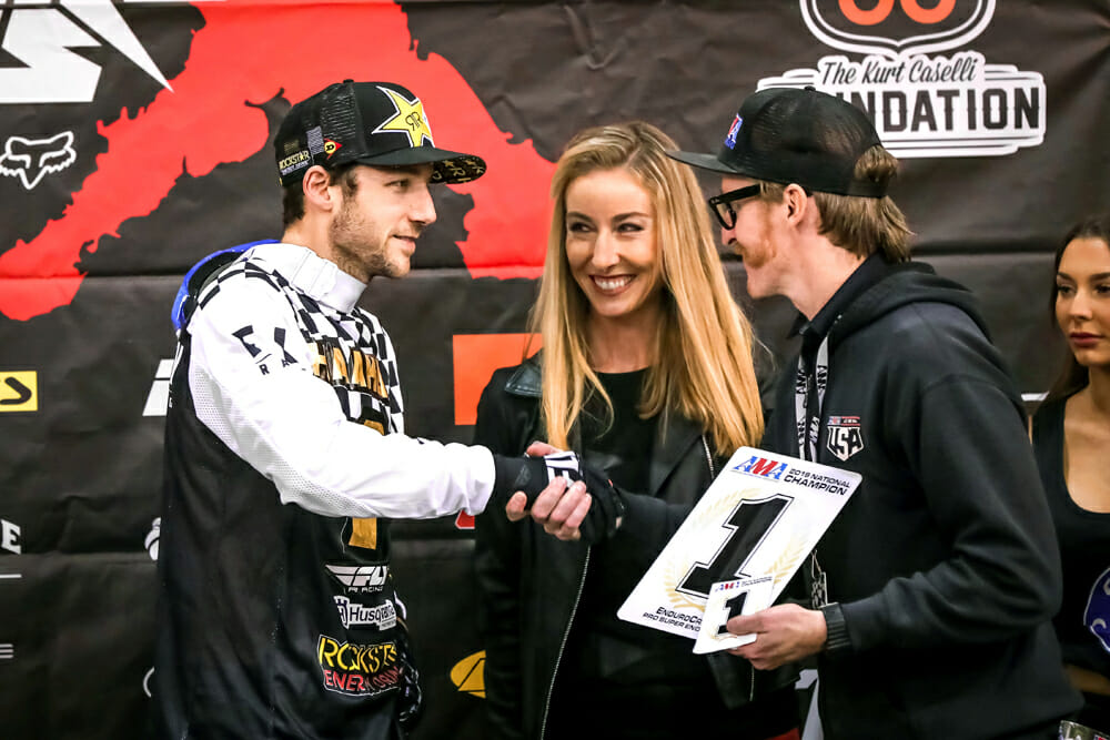 Colton Haaker accepts his latest number-one plate from AMA Off-Road Racing Manager Erek Kudla and EnduroCross announcer Laurette Nicoll.