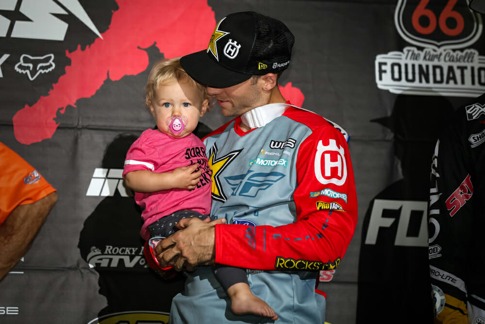 Colton Haaker shows off his daughter, London, on the podium.