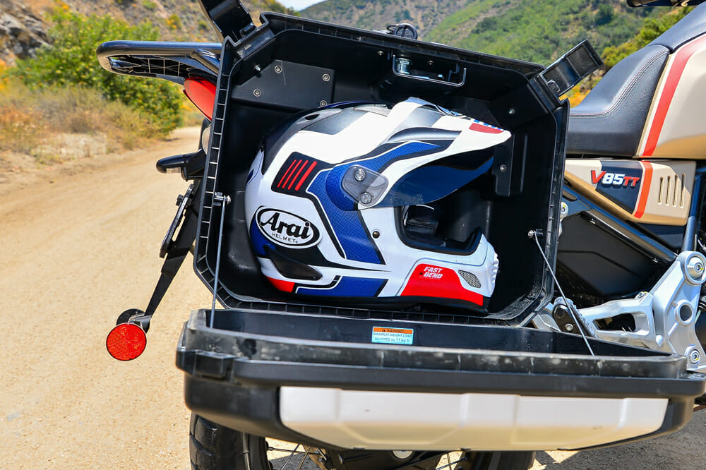 The 2020 Moto Guzzi V85 TT Travel with a helmet in the side case.