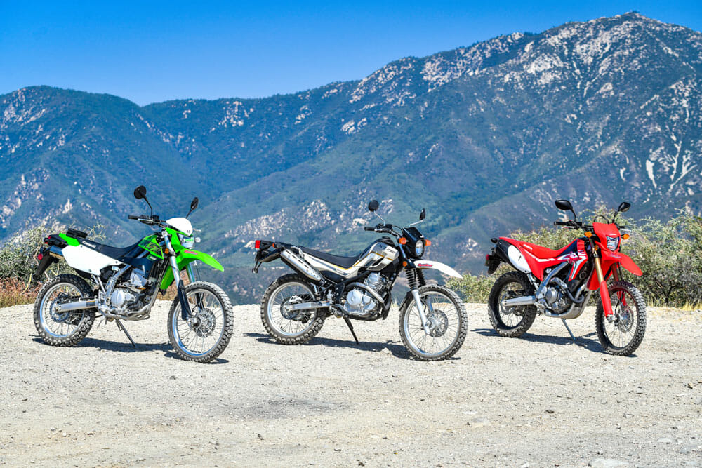 Kawasaki KLX250, Yamaha XT250 and 2020 Honda CRF250L parked with mountains in background