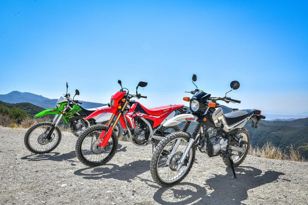 Kawasaki KLX250, 2020 Honda CRF250L and Yamaha XT250 parked