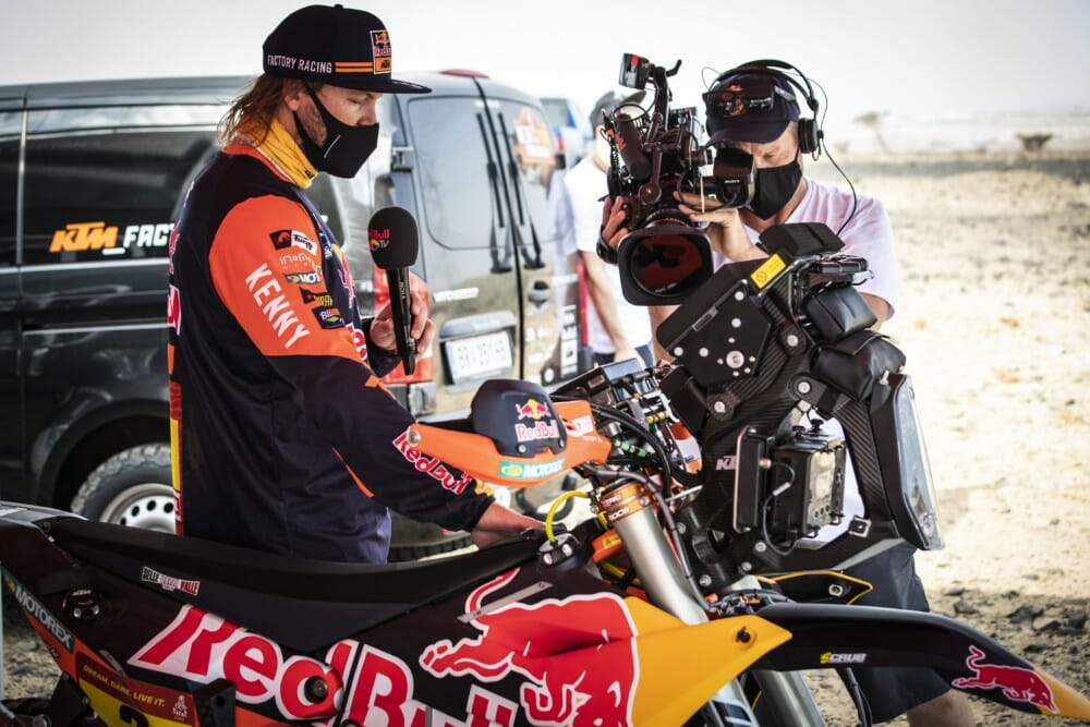 Toby Price shows the details of his Red Bull KTM Factory Rally Bike to a camera crew
